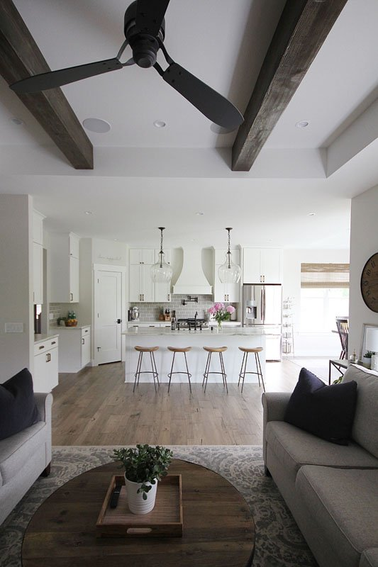 large open, but dark kitchen and sitting area painted white with wood ceiling beams