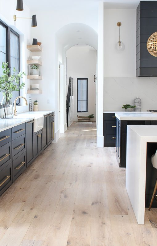 white kitchen with bright natural light and dark cabinets that leads into a hallway