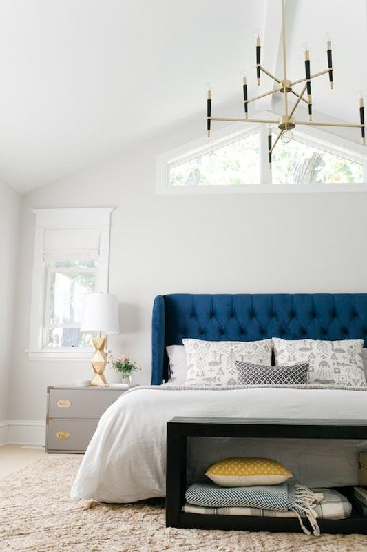 white bedroom with blue headboard and yellow and gold accent pieces