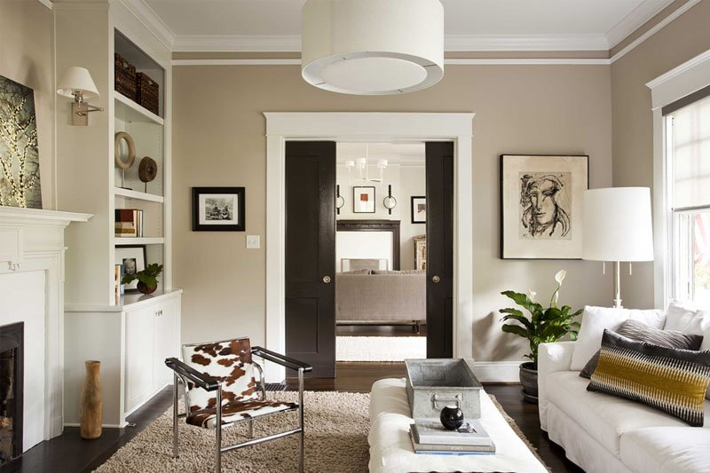 Cozy living space with Kilim Beige on the walls, wood flooring, sliding wood doors, beige rug and cow skin chair.