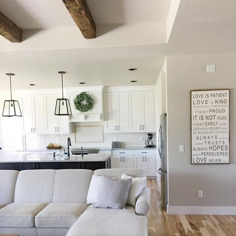Sherwin Williams Accessible Beige separates this living room from the white kitchen in this open concept living space.