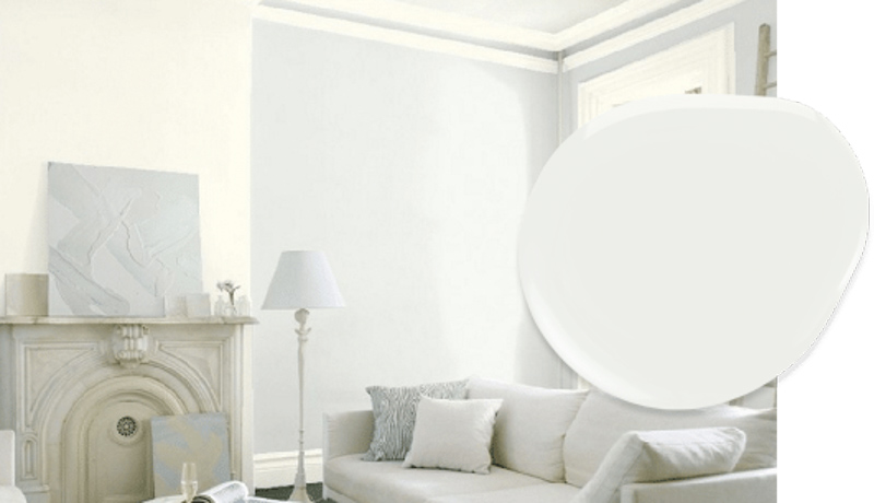 Monochromatic sitting room with marble fireplace, using Decorator's White on the walls to contrast with layered shades of white.