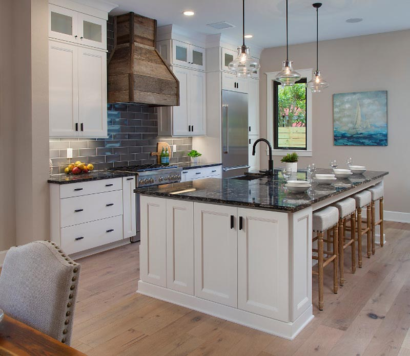 Kitchen with Sherwin Williams Accessible Beige walls, white cabinets and dark gray tile backsplash.