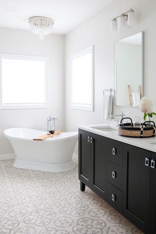 Soft and airy bathroom with Silver Satin paint on the walls, white trim, white bathtub and white and gray mosaic floor tile.