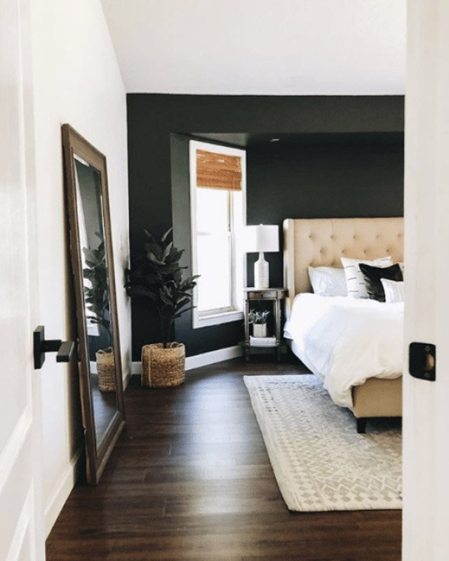 Bedroom with soft black accent wall, paired with pure white walls and rich brown hardwood floors.