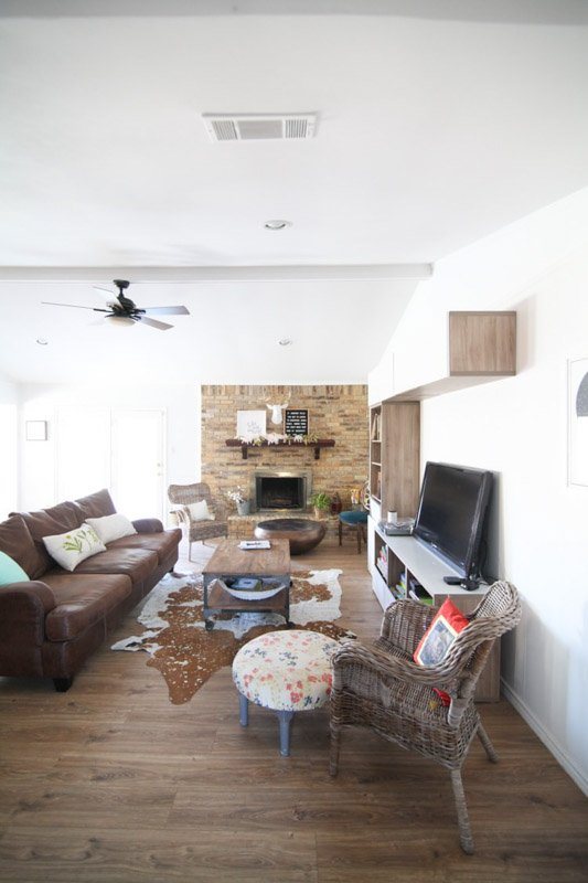 Texas-chic ranch style living room. Decorator\'s White walls create a clean backdrop to a variety of textures like leather, wicker and cow skin in the decor.