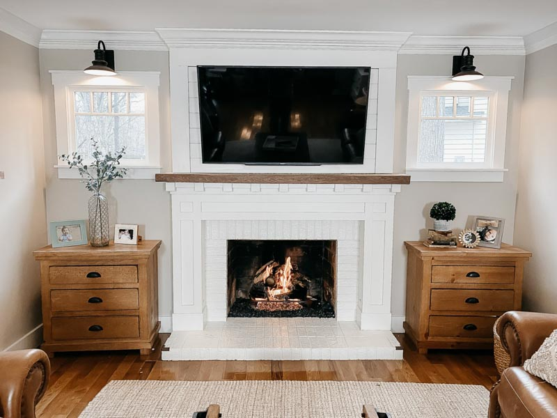 Cozy living space with a white brick fireplace, white trim on the windows and wooden end tables.