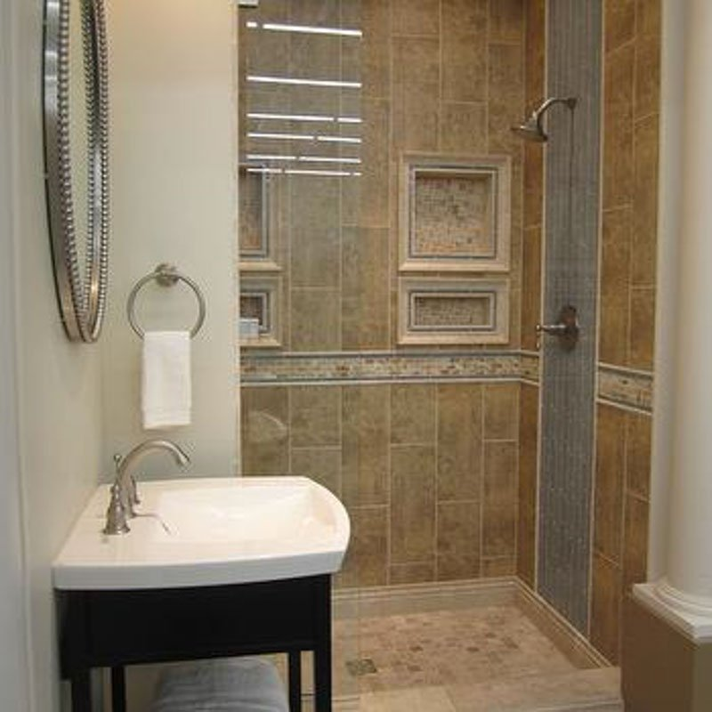 Tuscan style bathroom with dusty blue tile accent and dark wood pedestal sink.