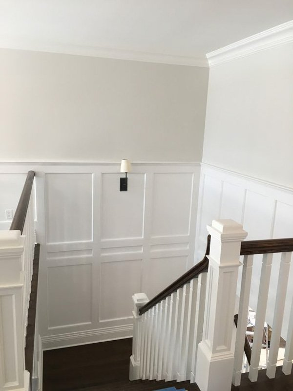 Staircase with white wainscoting and Benjamin Moore Silver Satin on the walls.