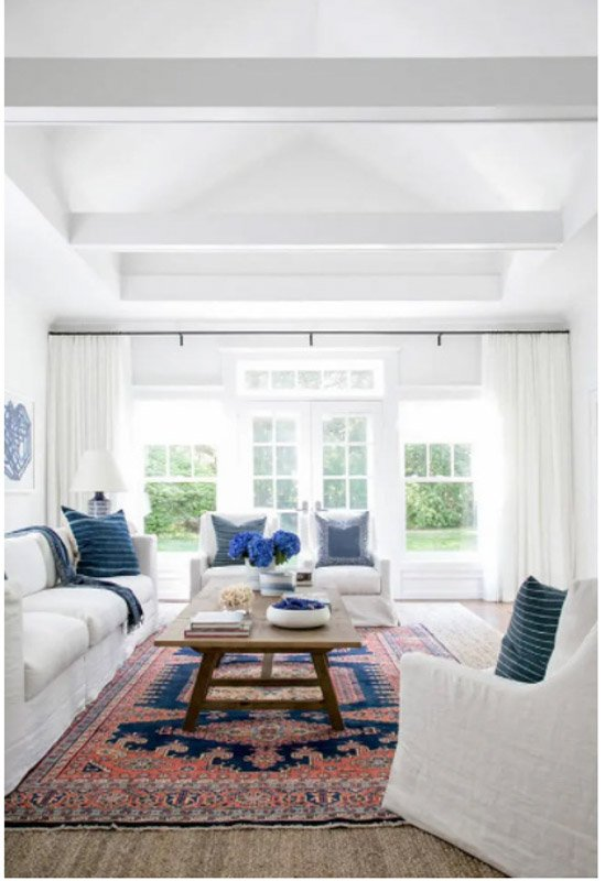 Bright white sitting room with natural light coming through the windows, a colorful rug and blue decor accents.