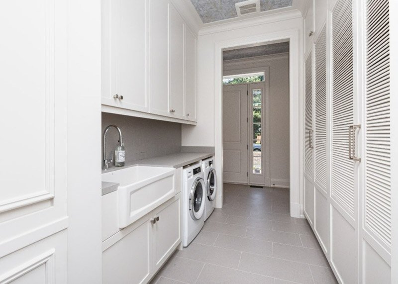 Laundry room with Silver Satin cabinets, gray backsplash and gray flooring.