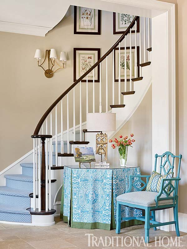 Elegant entryway with sweeping warm wood banister, blue carpet on the stairs and turquoise accents.