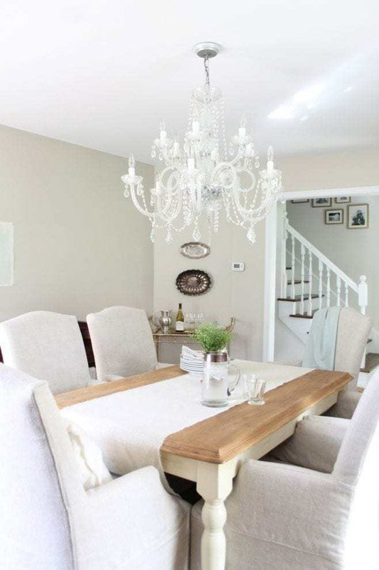 Dining room with white crystal chandelier and Sherwin Williams Accessible Beige walls.