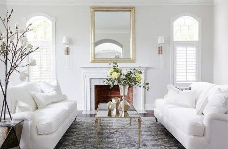 Elegant sitting room with marble and brick fireplace, gold framed mirror, white couches and Decorator's White walls.