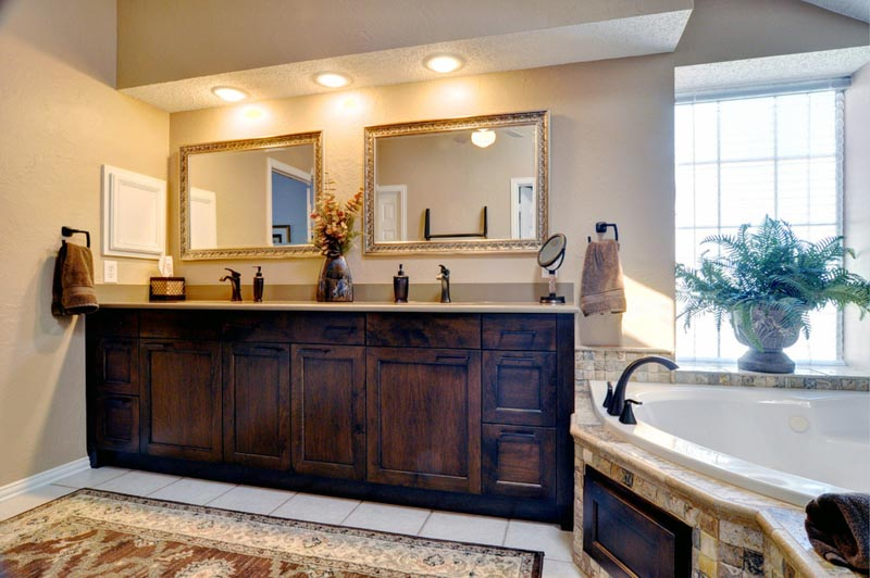 Bathroom with warm wood double vanity, gold framed mirrors, warm recessed vanity lighting and large bathtub.