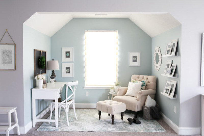 Pale, soft reading nook with SW Rainwashed walls, white ceiling and trim, a white writing desk and cream-colored reading chair and ottoman.
