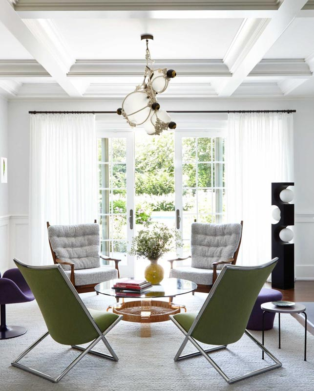 Midcentury modern styled sitting room with French doors, white curtains and white walls and ceilings.