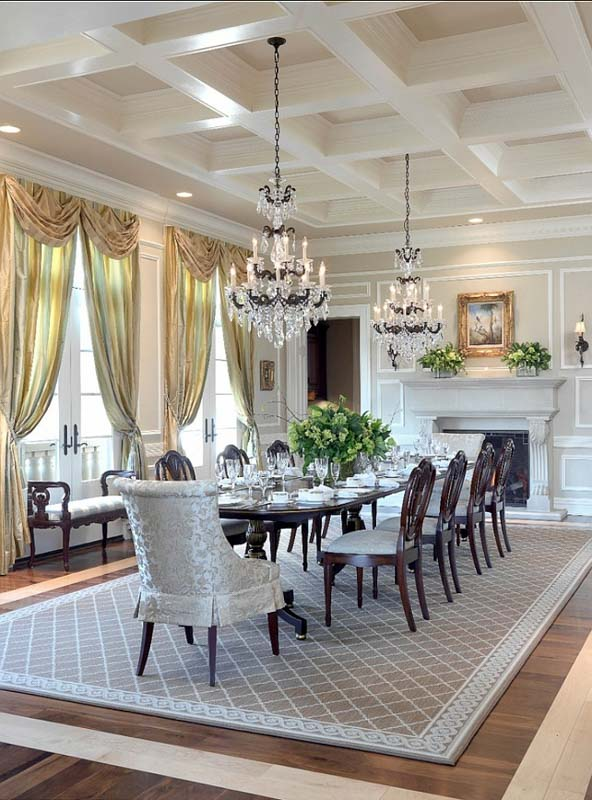 Lavish dining room with intricate architectural details, chandeliers, yellow curtains and warm wood furniture.