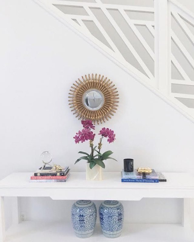 Simple white staircase space with white bench and bohemian decor accents.