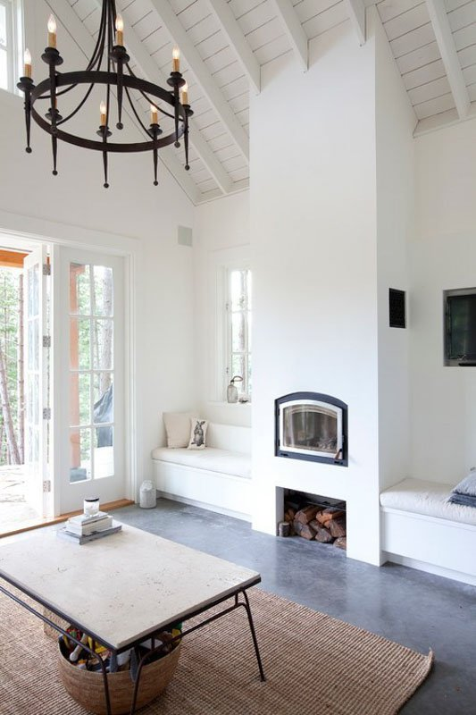 White space with vaulted ceilings, fireplace and wrought iron chandelier.
