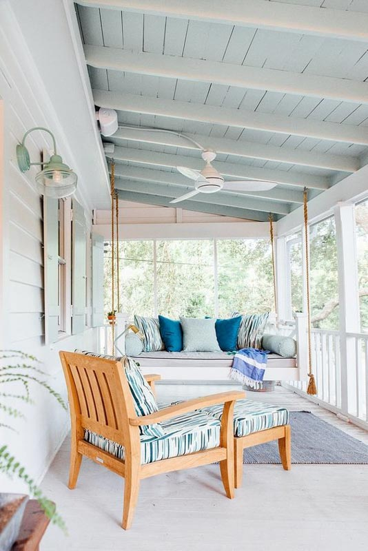 Coastal-themed covered porch with Rainwash paint under the awning, contrasting with white beams and beachy furniture.