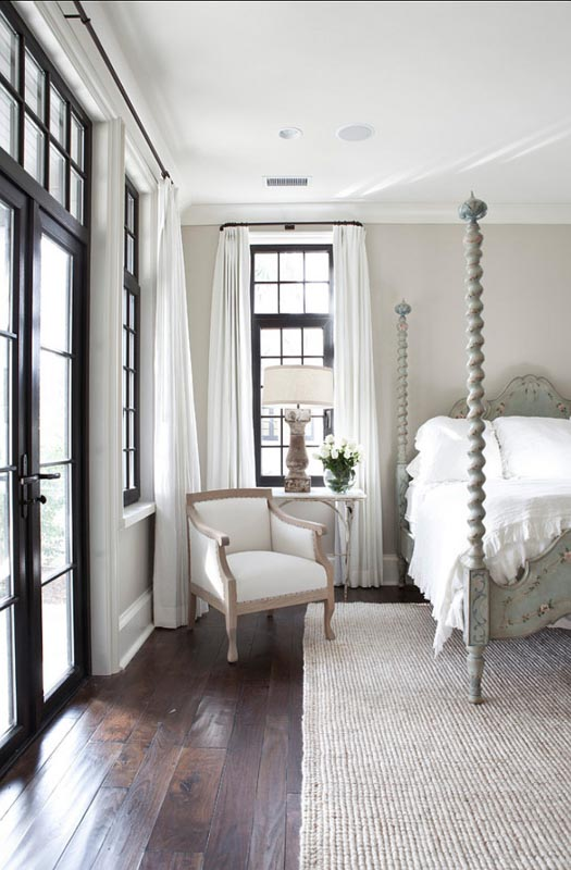 Bedroom with Sherwin Williams Accessible Beige walls, neutral color palette and black framed windows.