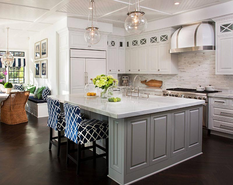 Kitchen with mindful gray island and white cabinets topped with marble
