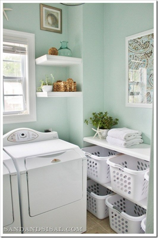 Laundry room with SW Rainwashed walls, white open shelving, white washer and dryer and white storage bins.