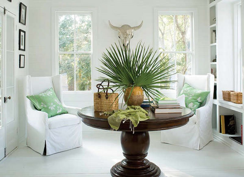 Cozy, white sitting room with faux cow skull and green decor accents.