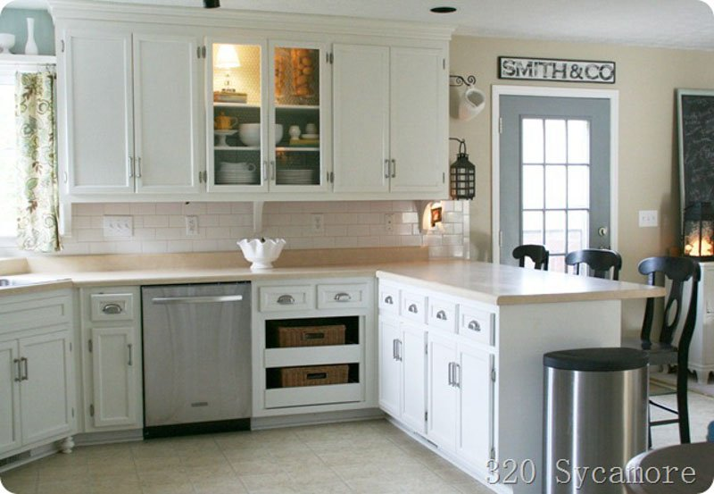 Open kitchen with white cabinets, Kilim Beige on the walls and a blue outside door.
