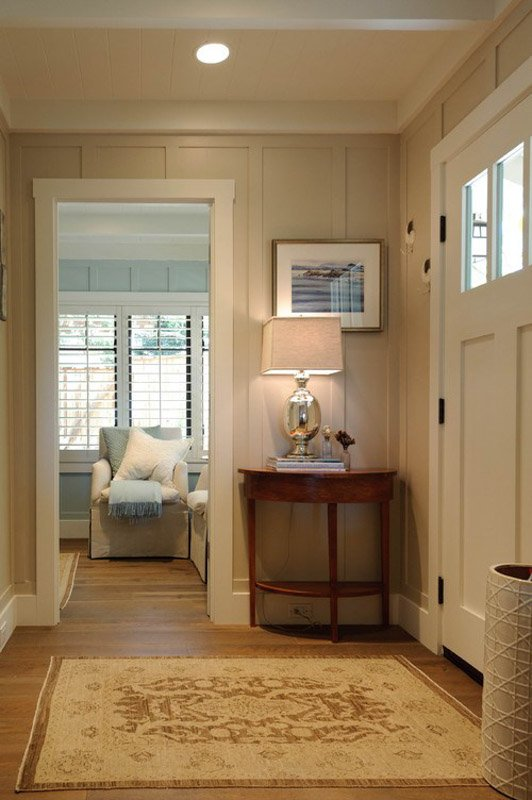 Entryway with soft lighting, paneled walls and white trim.