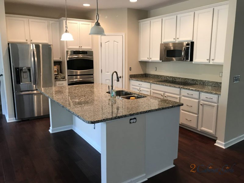 Kitchen cabinets get an update with Silver Satin paint in this kitchen with nickel appliances and granite countertops.