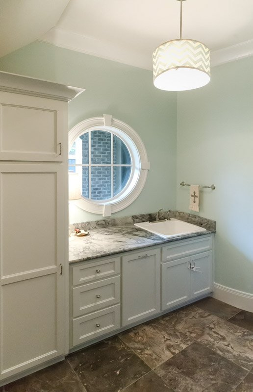 Simple, elegant bathroom with Rainwashed walls, circular window, white cabinets and marble countertop.