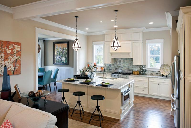 Open concept floorplan with a large kitchen island and three black barstools.