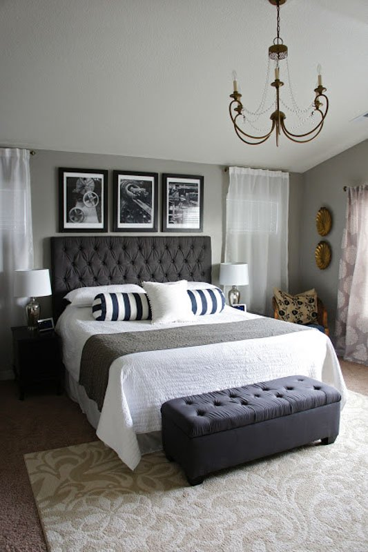 Cozy bedroom with a vintage chandelier and varying shades of gray.