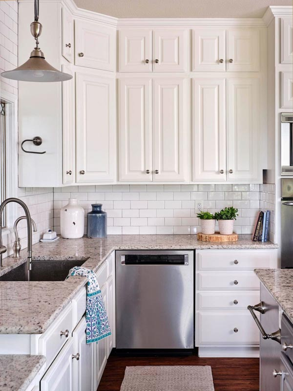 Kitchen with sparkling white subway tile backsplash, warm granite countertops and white cabinets.