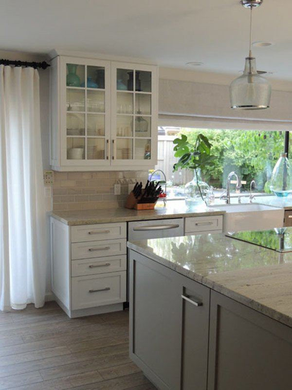 Kitchen with neutral color palette, white cabinets and gray kitchen island.
