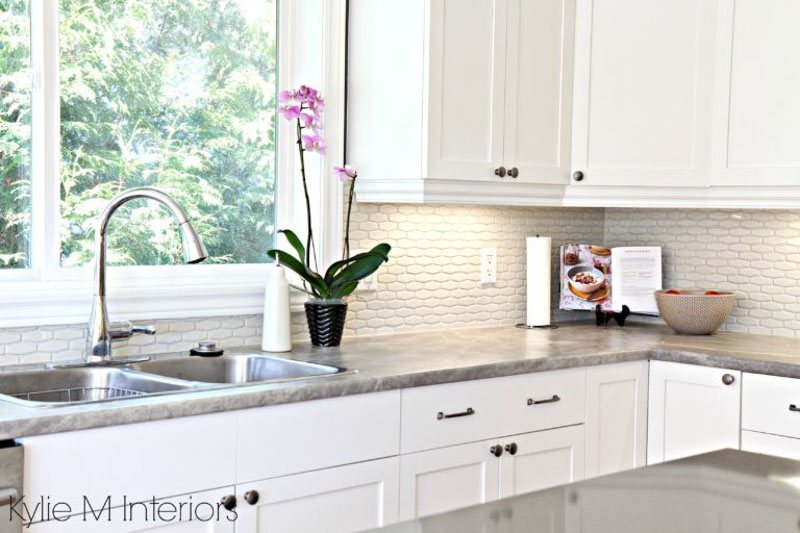 Benjamin Moore Cloud White cabinets and trim pop against gray stone countertops and off-white tile backsplash.