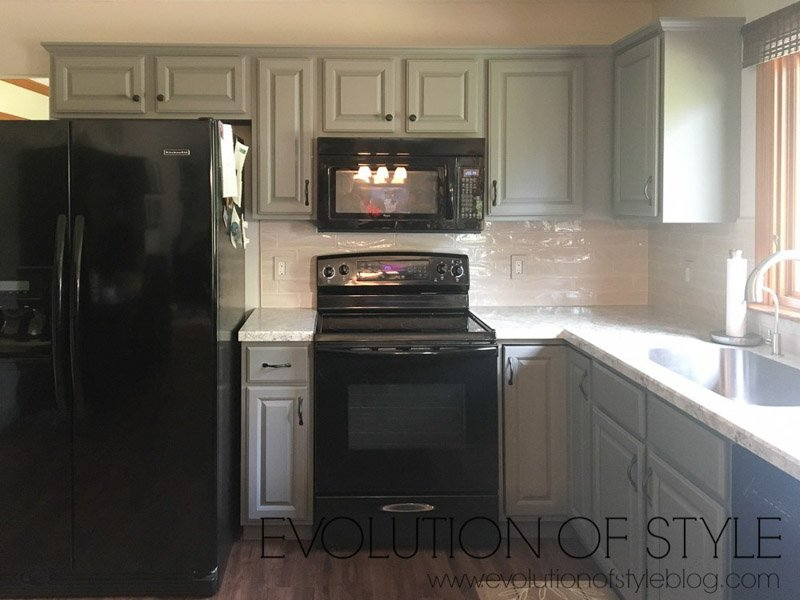 Kitchen with gray cabinets with green undertones, black appliances and light colored backsplash.