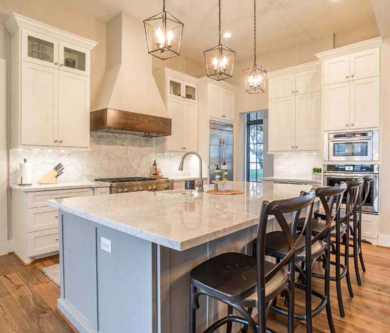 Beautiful kitchen with Dorian Gray kitchen island, blush wall paint, white cabinets and marble backsplash and cabinets.