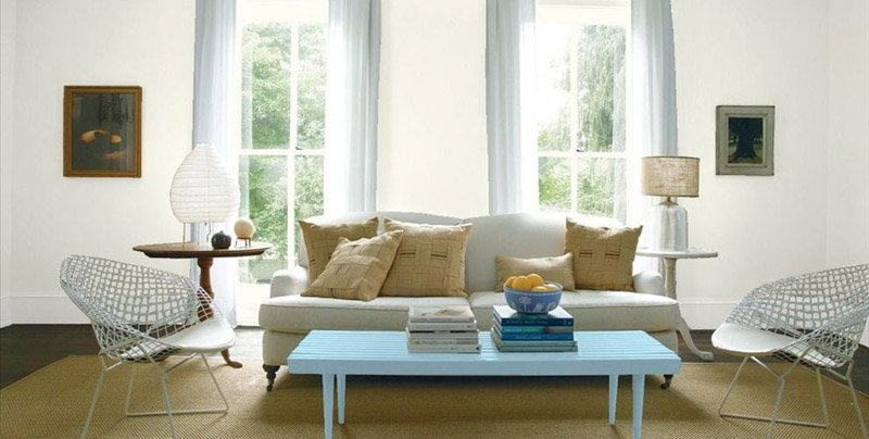 Benjamin Moore Cloud White pairs well with the pale blue-gray of the curtains and sofa in this living space.