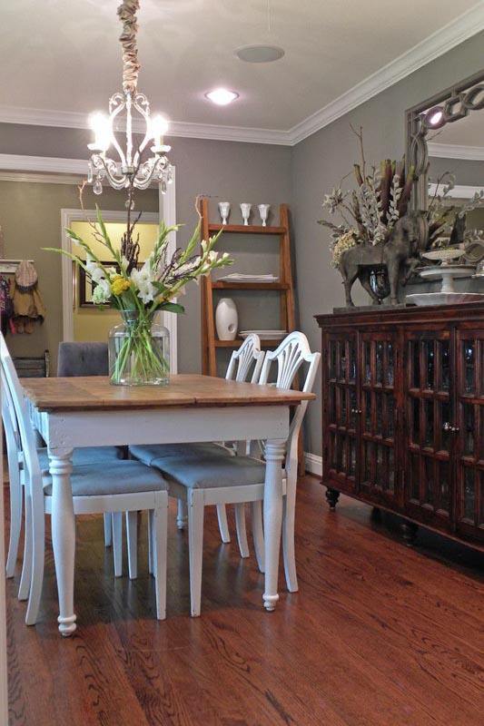 Dining room with gray walls and white trim and warm wood accents.