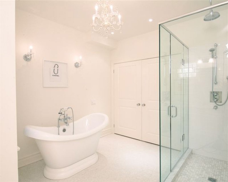 All-white bathroom with standalone tub, walk-in glass shower and chandelier.