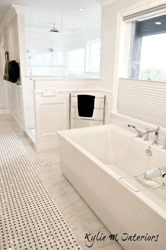 Long, narrow bathroom with marble and black tile flooring, standalone tub and Benjamin Moore Cloud White walls and wainscoting.