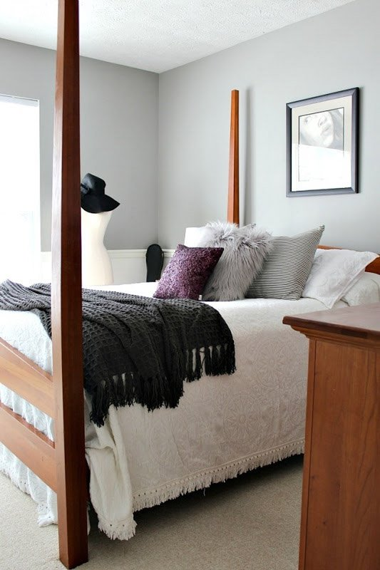 Dorian Gray paint shade with purple undertones complement a soft bedroom palette of white, gray and purple, with warm wood furniture.