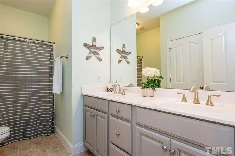 Dorian Gray painted bathroom vanity paired with pale sea foam green walls.