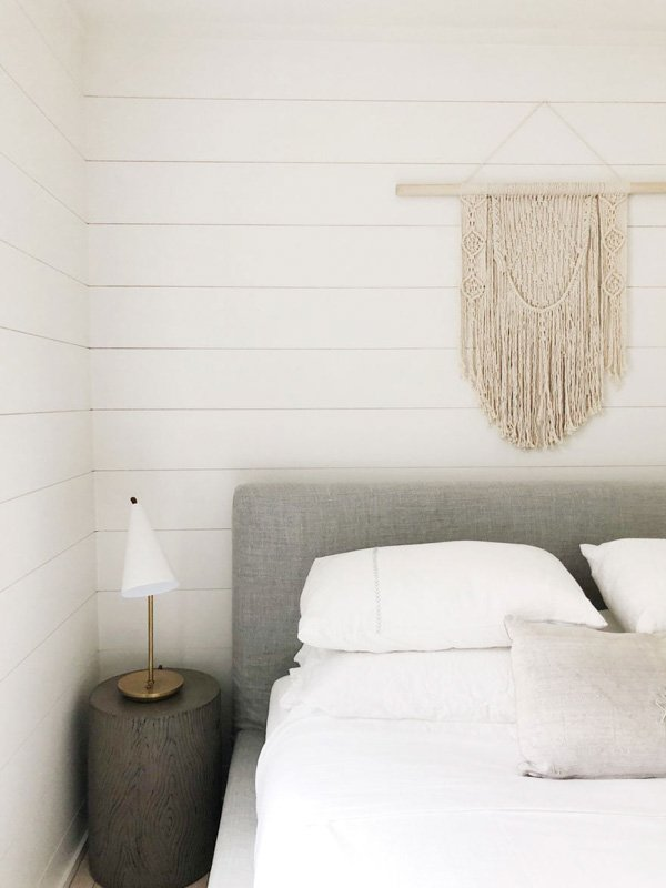 Cloud White shiplap is the most wonderful backdrop for this light gray upholstered headboard and macrame wall hanging.