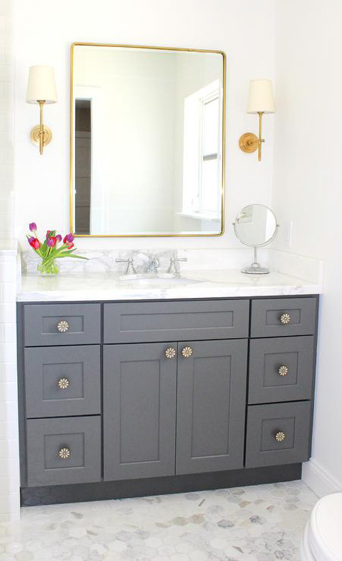 Bathroom with gray vanity cabinet, gray marbled countertop, Cloud White walls and gold accents.