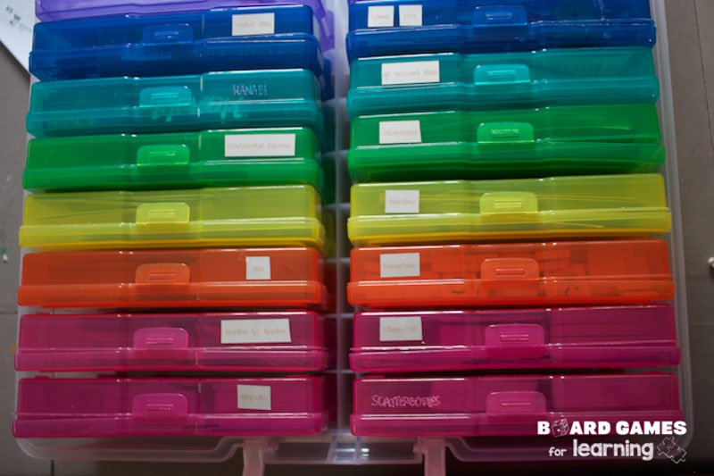 Colorful photo organizing boxes storing board game pieces.