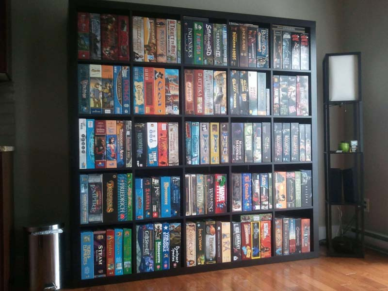 Large bookcase full of board game boxes stacked vertically to maximize storage space.